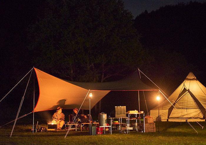 夜に灯りの灯ったテントの写真