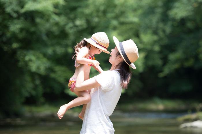 川で子供を抱きかかえるお母さんの写真