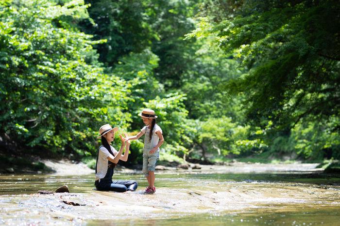川で遊んでいる親子の写真