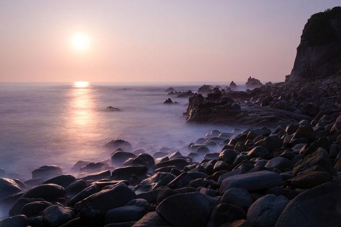 夕日に照らされた海と岩場の写真