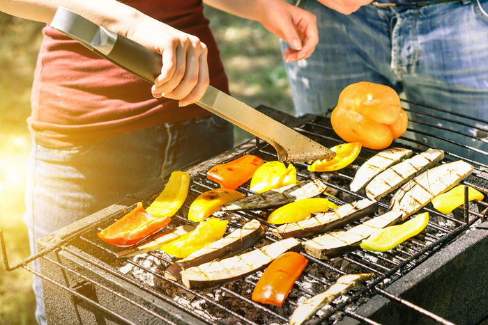 バーベキューで食材を焼いている様子の写真