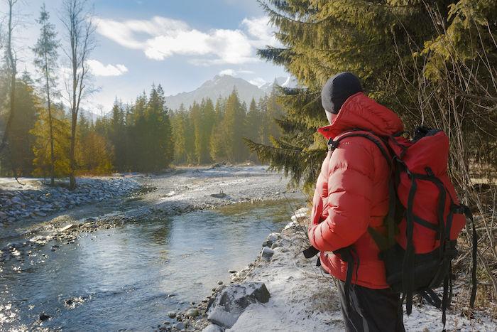ダウンジャケットを着て川を眺めている男性