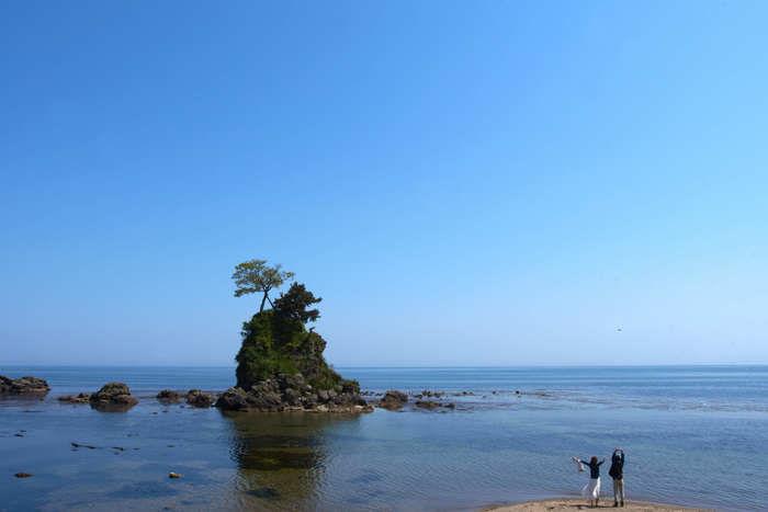 綺麗な海を眺めているカップルの写真