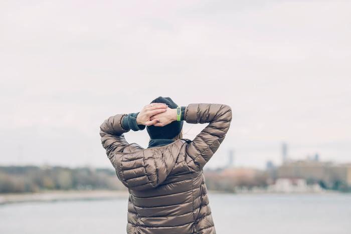 ダウンジャケットを着て海を眺めている男性の写真