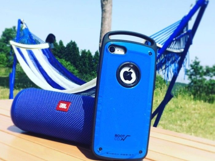 テーブルに置いてあるブルーのスピーカーとiPhone