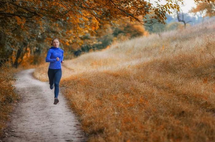 紅葉した草原の横を走っている女性の写真