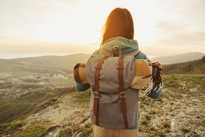 山頂で夕日を眺めるリュックを背負った女性