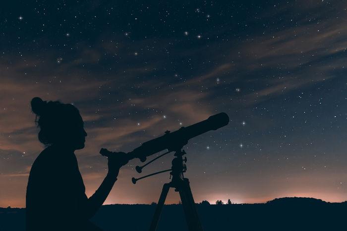 望遠鏡で夜空を見上げる女性