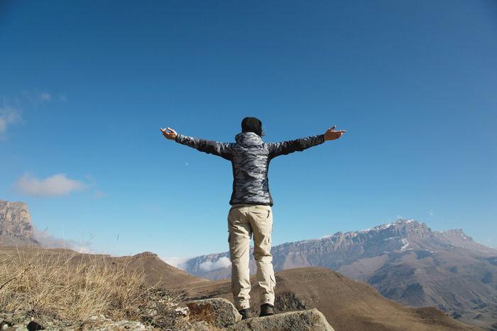 ダウンを着て山の山頂で伸びをしている人の写真