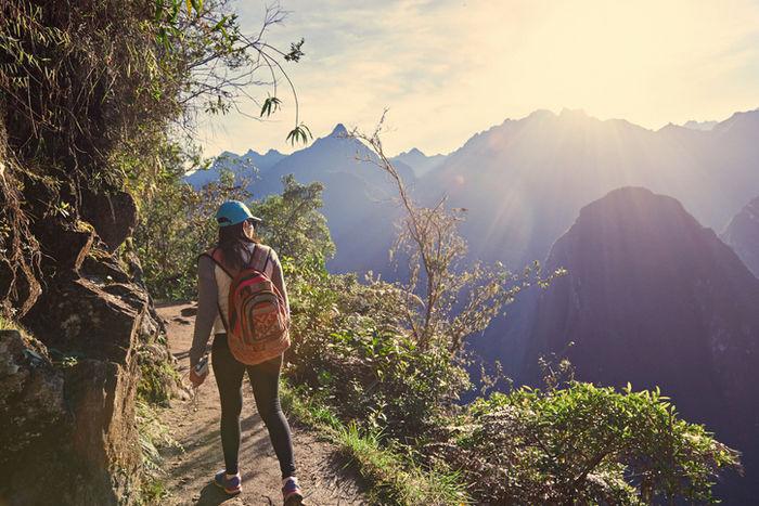 山のハイキングコースを歩いている女性の写真