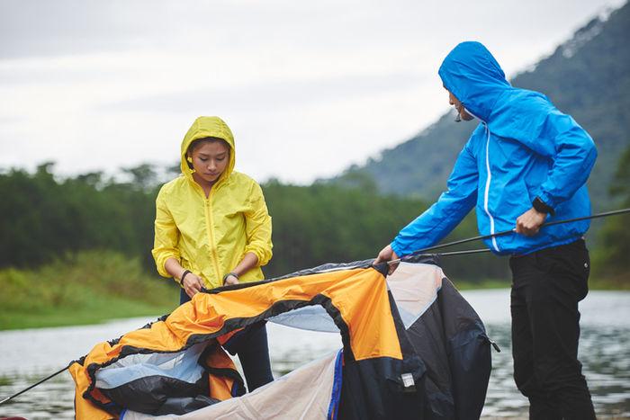 レインウェアを着てテントを組み立てている写真