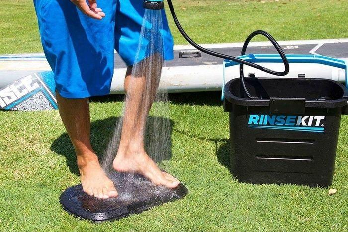 簡易シャワーで足を流す男性