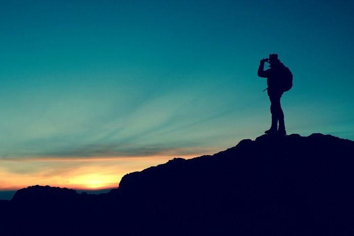 夕日を高台から見ている人の写真