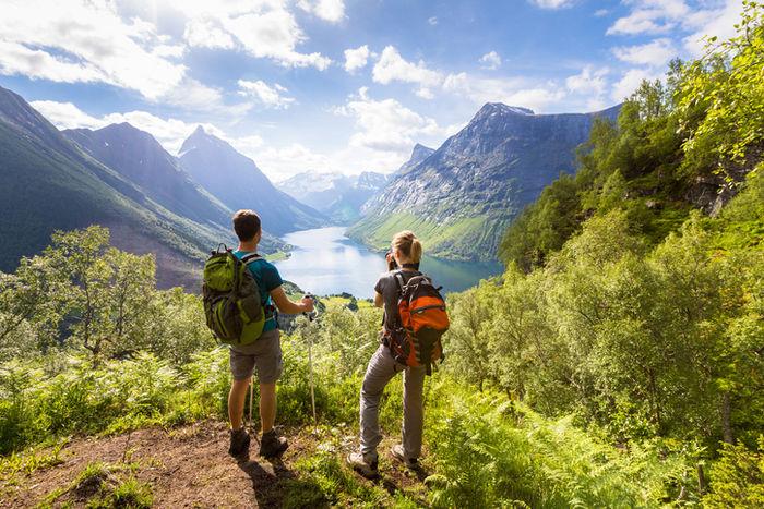 リュックを背負って湖を眺めているカップル