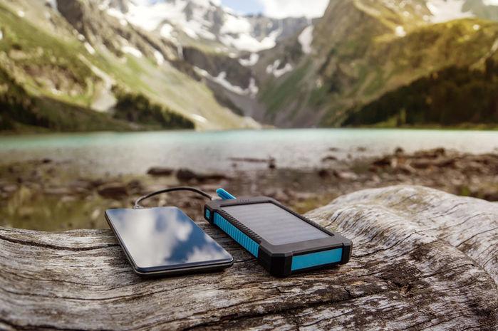 山でモバイルバッテリーを使って携帯を充電している写真