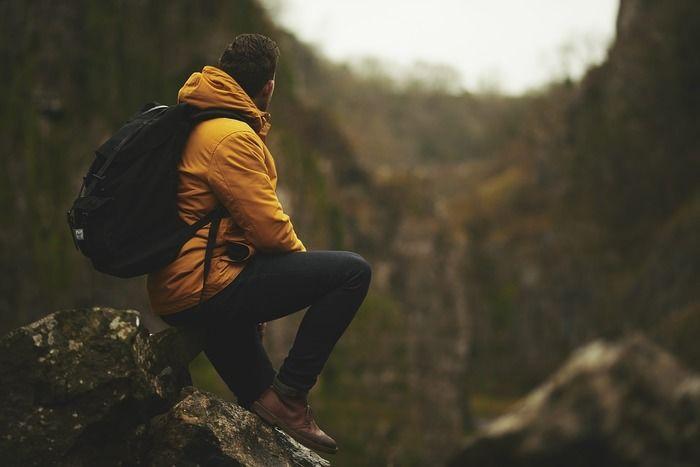 大きな岩に座って遠くを眺めている男性