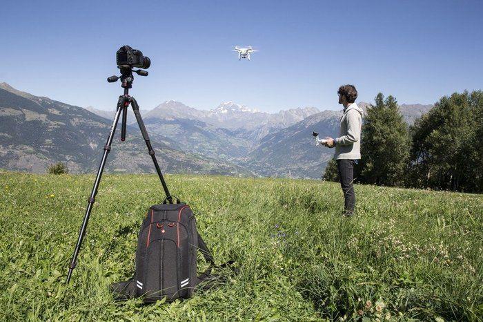 山の草原でドローンを飛ばしている男性