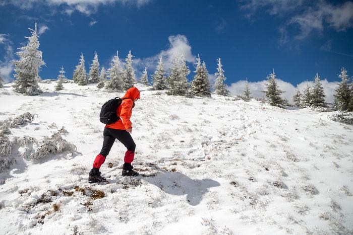 テックジャケットを着て雪山を登っている人