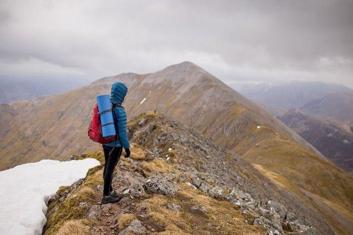 山頂でリュックを背負って景色を見ている人