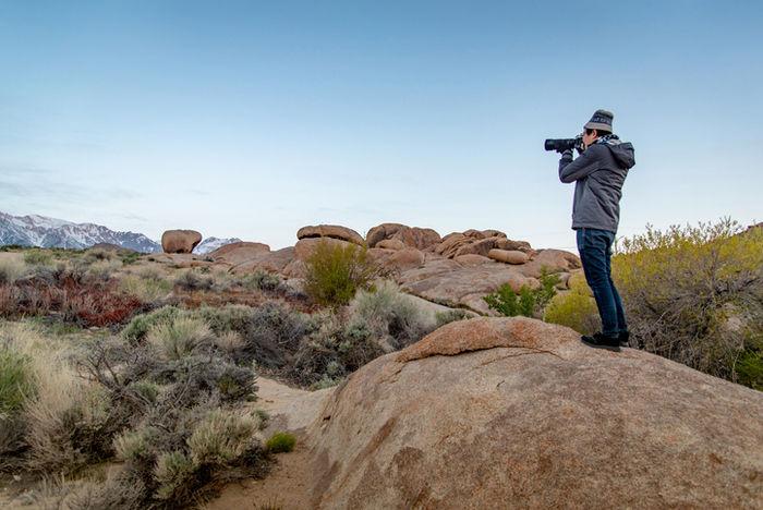 カメラで自然の景色を撮影している男性