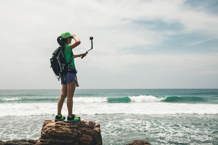 海でゴープロでセルフィーを取っている女性