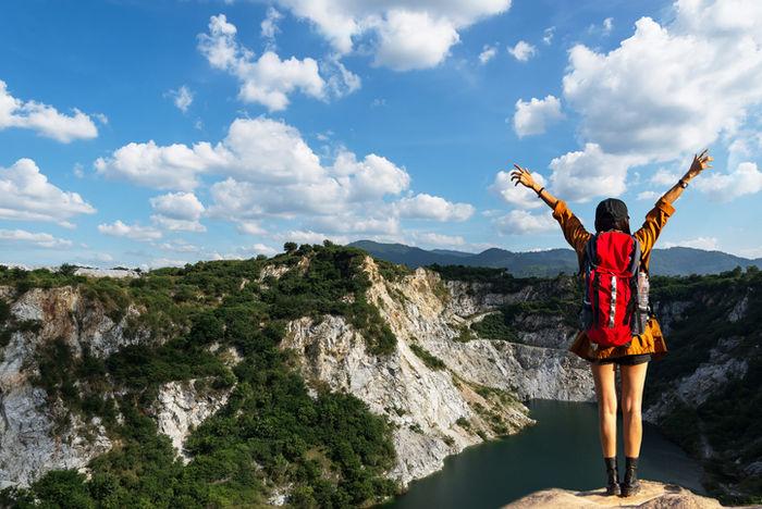 ハイキングリュックを背負って山頂に立っている女性