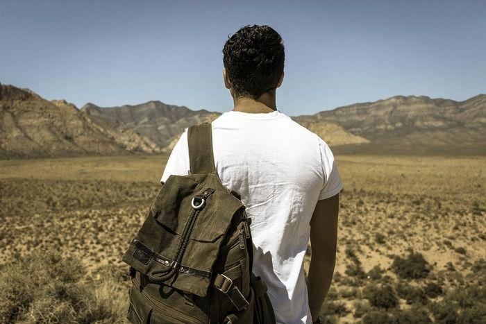 砂漠地帯でリュックを背負っている男性の後ろ姿