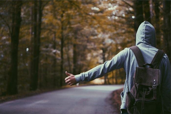 パーカーを着て山道に立っている男性の写真