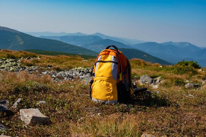 山頂の草の上にリュックが置いてある写真