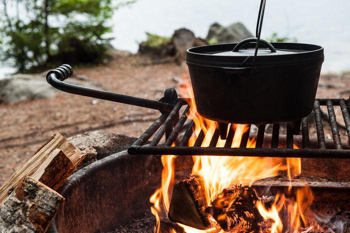 焚き火で鍋を温めている写真