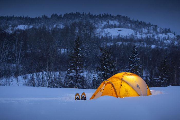 雪上にテントを貼って冬キャンプをしている様子の写真