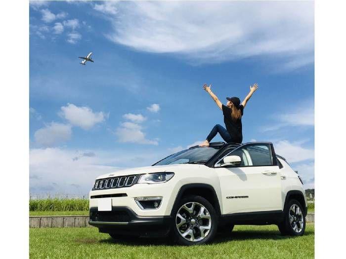 Jeepの上で飛行機を眺める女性