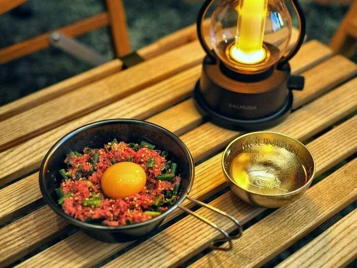 シェラカップに盛ったコンビーフユッケと日本酒