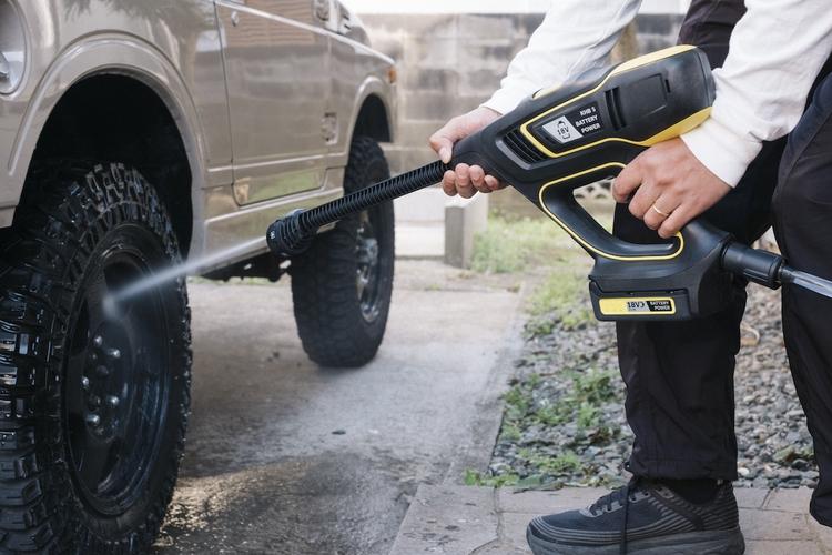 高圧洗浄で車のタイヤを洗う