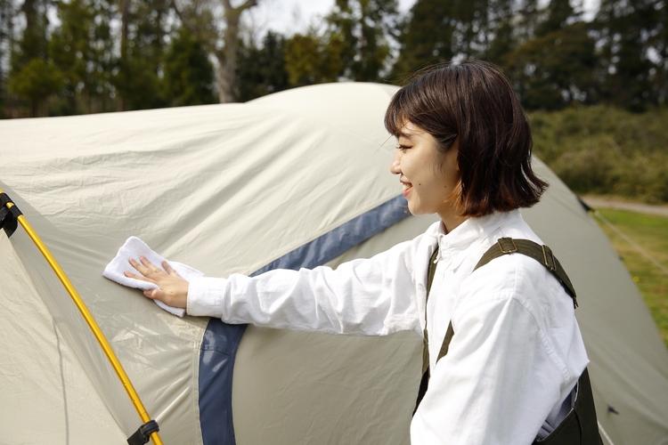 テントのフライヤーの表面を布で拭いている様子