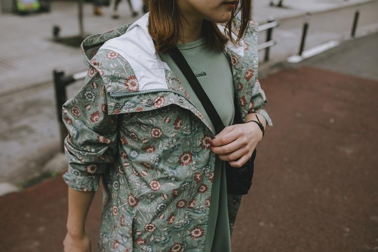 花柄のグリーンのアウターを着ている女性