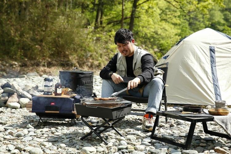 焚き火台で肉を焼く男性
