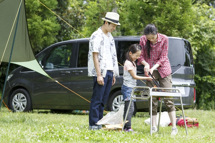 オートキャンプ場でバーベキューをしている親子