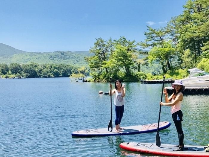 快晴の湖上でそれぞれのSUPに立っている2人の女性