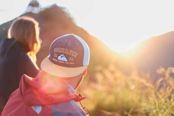 自然の中で山に沈む夕日を眺めるカップル