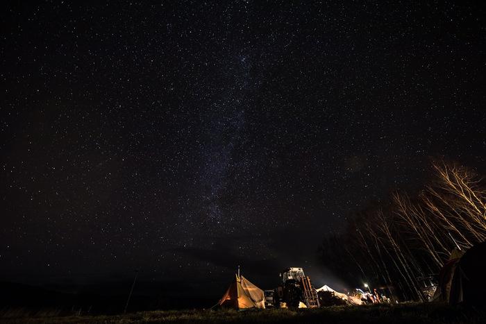 満天の星空の下のテント数張りと右側に木立