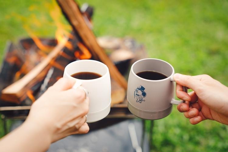 焚き火を前にコーヒーのカップを持っているところ