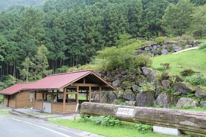 緑濃い山を背後に赤い屋根の炊事場と丸太に記された「ゆめのもり」の看板