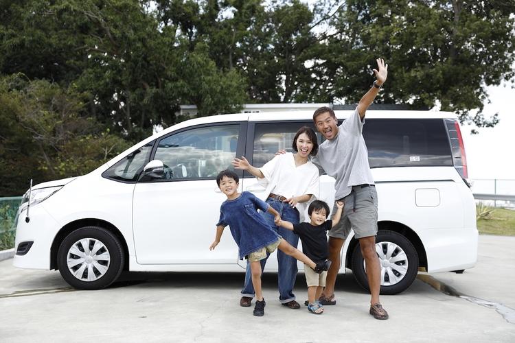 車の前でポーズをとる家族
