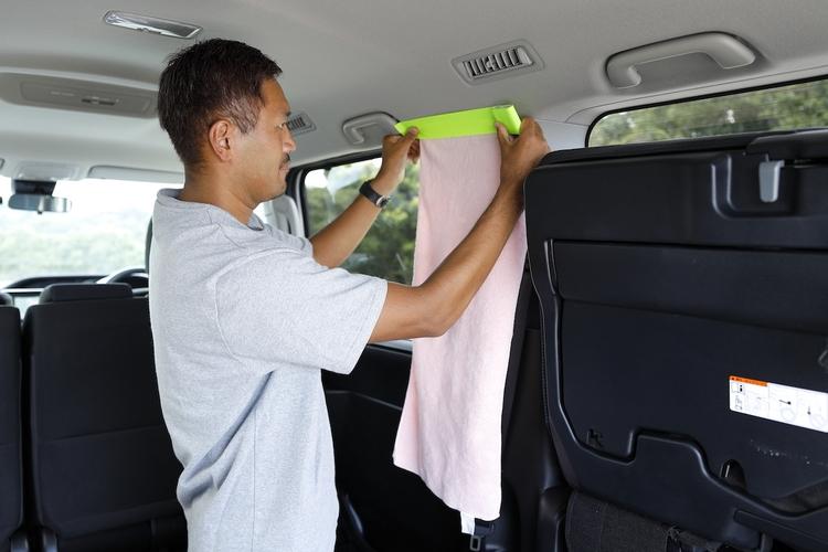 タオルの端にアウトドアテープを貼り、車のカーテンにしているところ