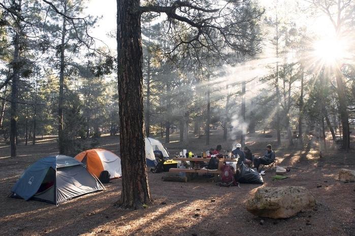林間に3張のテントと木のベンチやテーブルでくつろぐ数人
