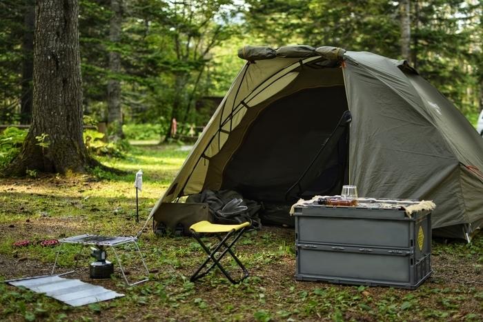 林間に設営されたカーキ色のテントやボックスコンテナ、小型チェア