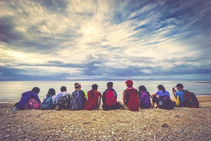 夕暮れのビーチに座って並んでいるリュックを背負った少年少女の後ろ姿