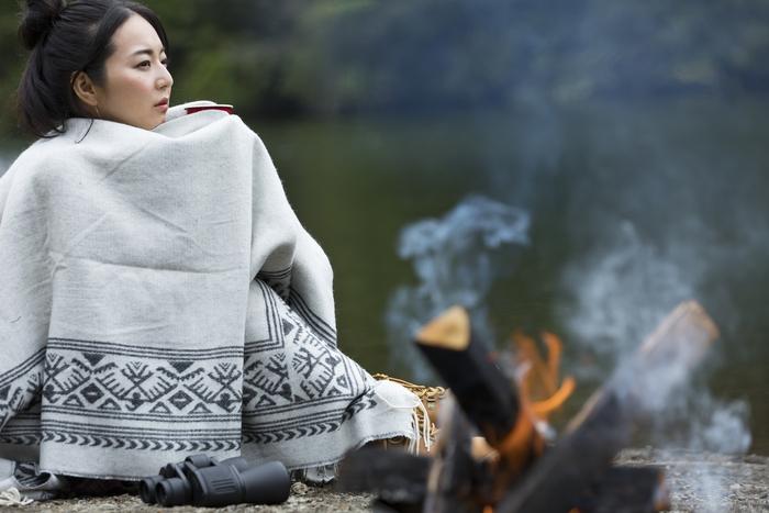 ブランケットにくるまりながら焚き火にあたる女性