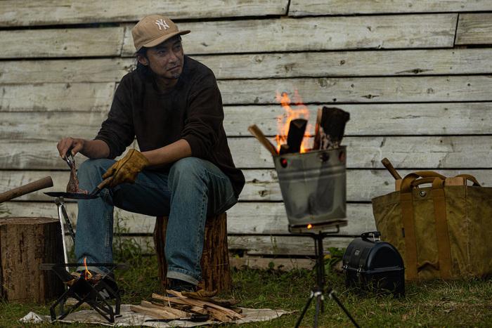 焚き火をしながら料理する猪野さん